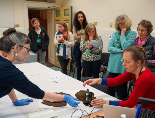 Examining surviving 16th century knitted caps with museum curator Ruth Battersby Took (far left) with Ninya manning the microscope. Photo by Challe Hudson