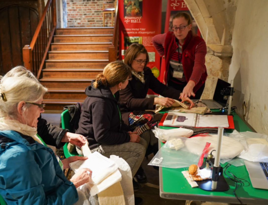Examining samples of reconstructed knitting with Jane in the undercroft of Strangers Hall. Photo by Challe Hudson